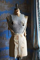 Old tailors' dummy in front of toil de jouy wallpaper in elegant, country-house interior
