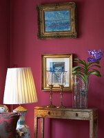 Vase of flowers next to candlesticks on vintage console table below gilt-framed pictures on claret wall; floor lamp with pale fabric lampshade