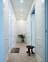 Narrow hallway with tall, white, traditional-style interior doors, striped wallpaper and rustic wooden stool on herringbone parquet floor