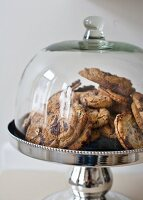 Biscuits on silver cake stand with glass cover