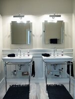 Twin vintage washstands on metal frames below two illuminated mirrors on wall with black rugs on white wooden floor