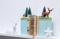 Hand-crafted bookends with winter motifs decorated with miniature deer and tiny fir trees