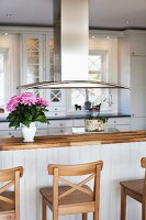 Wooden bar stools at kitchen counter below stainless steel extractor hood in open-plan, country-house kitchen
