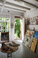 Artist's studio - painting utensils on table and pictures leaning against wall next to open door with view into garden
