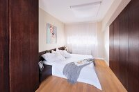 Elegant bedroom with contemporary ambiance; double bed with white covers and flat-fronted, dark wood fitted wardrobes