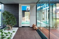 Glazed foyer with planted strip in contemporary house; view of indoor pool through glass door