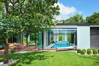 Sunny garden and terrace outside contemporary house with indoor swimming pool