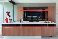 Long kitchen counter with wooden base cabinets an red-painted pendant lamp with strip-shaped housing in modern, open-plan kitchen
