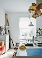 Workspace with collection of lampshades in apartment of young, designer couple