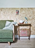 50s sofa and second-hand retro side table with magazine rack against wall clad in rustic chipboard panels