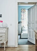 View from corridor with antique bureau into white IKEA bedroom with floor and wall in soft shades of blue