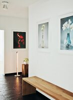 Minimalist wooden bench on slate-style floor covering in contemporary hallway with photos of flowers on walls