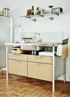 Modern kitchen sink unit with metal frame and wooden drawers below kitchen utensils on glass, wall-mounted shelf