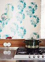 Saucepan on gas hob against wall with blue stencilled pattern on white background