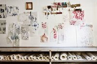 Sketches and reels of yarn hung on wall above shelf of rolled paper