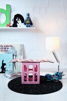 DIY stool made from skateboard bolted to pink drinks crate