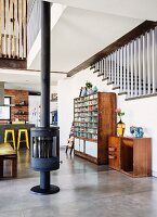 Free-standing wood-burning stove on concrete floor, sideboard and vintage shelving unit against staircase in open-plan interior