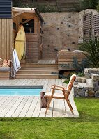 Outdoor pool with retro chair on wooden deck in garden and climbing wall on wooden platform in background