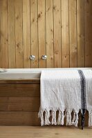 Towel hung over bathtub against wall clad in vertical wooden boards