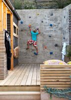 Boy on climbing wall adjoining wooden deck next to house