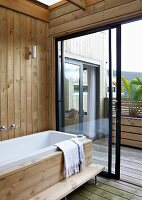 Bathtub against wood-clad wall, open, sliding terrace door and view of terrace
