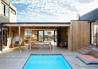Pool surrounded by wooden deck in front of loggia and modern wooden house