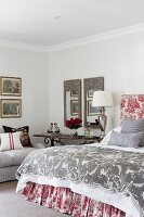 Bedroom in traditional, French style with toile de jouy textiles and classic lamp on antique side table