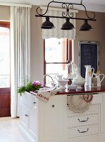 Free-standing counter with dark wooden top and white-painted base units below wrought iron pendant lamp with three black metal lampshades