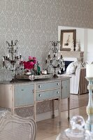 Vintage bureau and elegant candelabras with glass pendants against wall with pale, brocade-patterned wallpaper