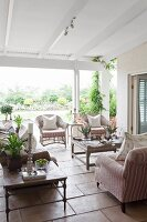 Roofed terrace with elegant wicker furniture, upholstered armchairs and coffee tables on tiled floor