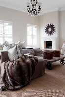Fur blanket on sofa and rustic, low coffee table on castors in living room with fireplace