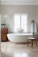 Free-standing, white, designer bathtub below window with louvre blinds and antique chair on elegant, tiled floor