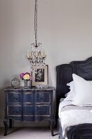 Chandelier with glass pendants above alarm clock and nostalgic picture on antique, black bedside cabinet with curved feet next to bed