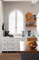Country-house-style kitchen; custom sideboard with drawers in front of arched window with interior shutters