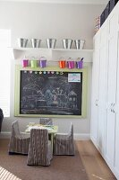 Children's table and chairs with striped loose covers below drawings on wall-mounted blackboard; colourful metal buckets hanging from bracket shelves above