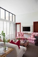 Armchairs with red and white, ikat-patterned upholstery and coffee table in interior with white, interior shutters on glass façade