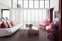 Lounge area with pale sofa and armchairs with red and white ikat-patterned upholstery around coffee table in front of white, interior shutters on glass façade