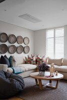 Comfortable corner sofa and round wooden coffee table below arrangement of shallow baskets decorating wall