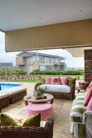Wicker outdoor furniture and ottoman with geometric cover on roofed terrace of holiday home