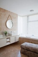 Long, modern washstand with twin countertop sinks next to fitted bathtub below window in elegant bathroom