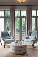 Two armchairs and pale ottoman in front of French windows