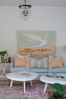 White coffee tables on vintage rug and scatter cushions arranged on pale blue couch below landscape painting on wall