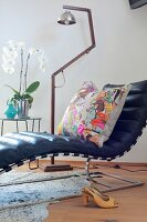 Designer couch with black leather cover and colourful scatter cushion in front of retro, stainless steel standard lamp