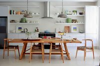 Solid wood dining table and chairs in open-plan kitchen with white fitted cabinets and open-fronted shelving