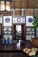 Kitchen counter in front of low installation with doors decorated with blue and white tiles and row of baskets on top