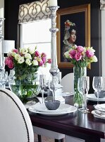 Table festively set with vases of flowers and silver candlesticks; painting on black wall in background