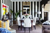 White upholstered chairs around table in dining room with black and white striped wallpaper