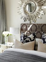 Scatter cushions on bed against upholstered headboard with ornate headboard below mirror with sunburst frame