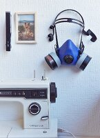 Detail of sewing machine below blue respirator mask and photo of dog on wall