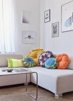 Various flower-shaped scatter cushions on pale, modern couch behind Thonet coffee table